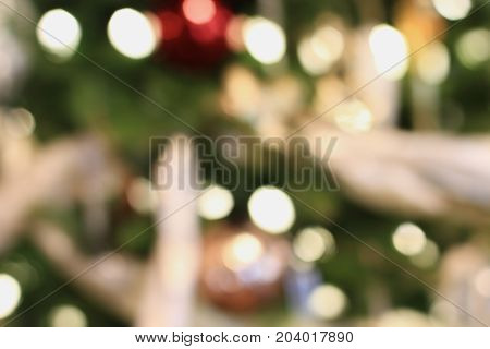 Abstract background of an out of focus Christmas tree with blurred bokeh lights background.