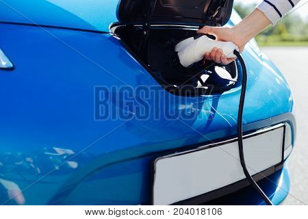 Eco friendly cars. Close up of an electric car charger being used for charging a modern electro car
