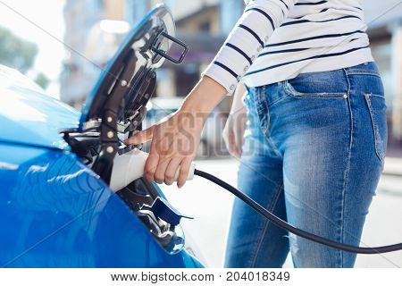 Innovations in car industry. Pleasant nice young woman holding a car charger and using it for her car while visiting a charging standing