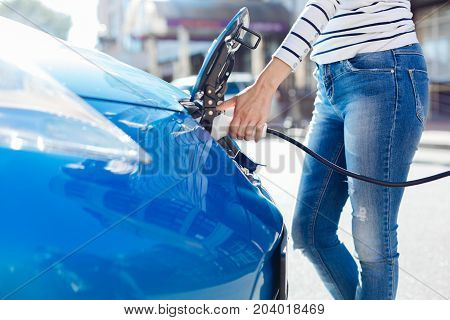 Ecological transport. Close up of a professional electro charger being plugged into the car while charging it with electricity