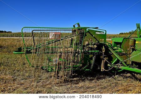 OSAKIS, MINNESOTA , September 8, 2017: The spring loaded bale thrower with a posted danger sign  in the chute is a product of the John Deere  Corporation headquartered in Moline, Illinois.