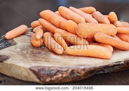 Baby carrots piled on top of a wooden cutting board over a rustic table..