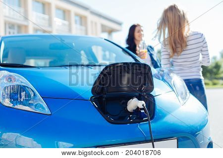 Charging process. Selective focus of an electric car charger being plugged into a modern electro car
