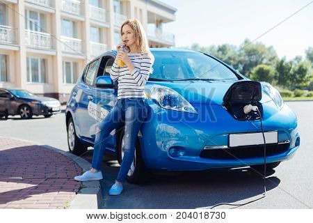 Recharging of battery. Attractive beautiful nice woman standing near her car and drinking orange juice while waiting for it to be charged