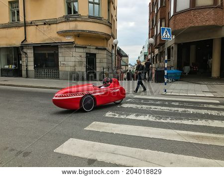 Oslo, Norway - 10 June 2017: Modern red Velomobile Mango Sport with driver in the old town