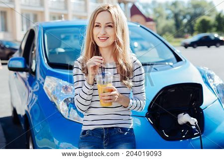 Positive mood. Delighted happy nice woman leaning on the car bonnet an smiling while holding orange juice