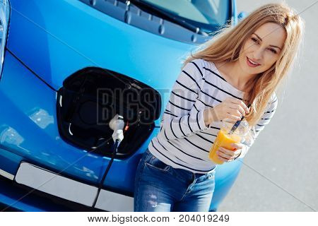 Electric car. Positive happy attractive woman visiting a charging station and drinking juice while waiting for her car to be charged
