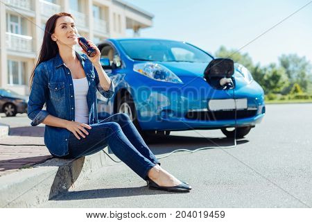 Pleasant rest. Delighted attractive young woman sitting on the sidewalk and holding a drink while waiting for her car to be charged