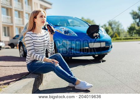 Auto owner. Pretty delighted young woman sitting in front of her car and drinking soda while waiting for it at the charging station