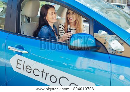 Pleasurable ride. Delighted positive happy women sitting in the car and talking to each other while having a nice ride