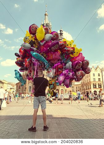Krakow, Poland - July 29, 2017 : Male street vendor sells colorful popular cartoon character helium balloons