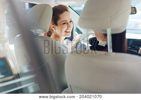 Great mood. Joyful happy attractive women riding in the car and laughing while being in the great mood