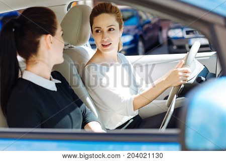 Female friends. Nice pleasant attractive businesswoman sitting behind the wheel and looking at her colleague while being in the car with her