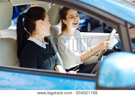Great joke. Happy cheerful delighted businesswoman sitting behind the wheel and laughing while talking to her colleague