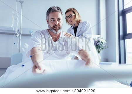 Doctor examining mature man in hospital bed. Patient sitting in bed with female doctor checking his heartbeats.