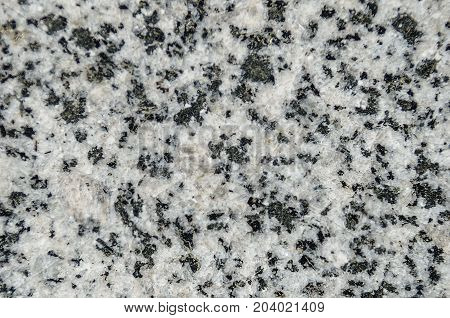 Facing material granite texture. Natural stone grey granite background texture. Bright hard grey granite rock texture. Grey granite stone background texture. Grey granite untreated surface. Facing material full frame horizontal granite texture.