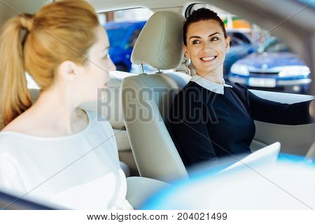 Where shall we go. Happy cheerful nice women looking at each other and deciding where to go while meeting together