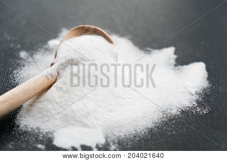 Spoonful Of Bicarbonate. Baking Soda, Sodium Bicarbonate, Nahco3. Wooden Spoon On A Black Background