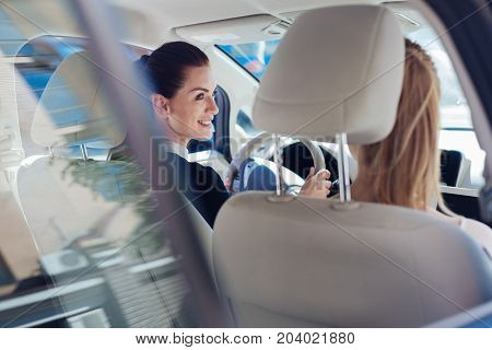 Successful businesswomen. Delighted nice happy businesswomen sitting in the car and looking at each other while driving to work