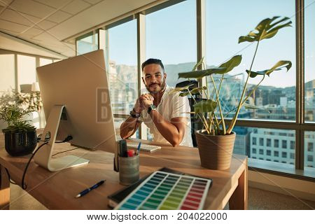 Portrait of handsome male entrepreneur sitting at his desk with desktop computer. Caucasian young man at his workplace looking at camera.