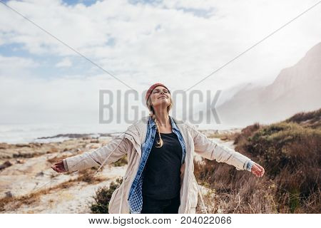 Young woman enjoying a day on the beach. Beautiful female enjoying a winter day on the seashore with her arms outstretched and eyes closed.