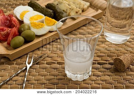 Glass and bottle of traditional drink Ouzo or Raki and appetizers on natural matting
