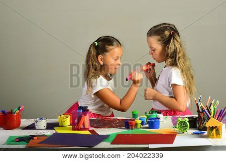 Girls With Concentrated Faces By Their Art Desk