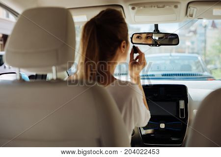 Time for some make up. Attractive pretty young woman looking into the rear view mirror and holding a mascara brush while putting on makeup