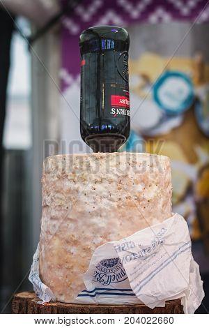 Utrecht Netherlands December 9 2016: Bottle of port stuck in a stilton cheese displayed on the food festival.