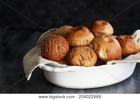 Fresh baked dinner rolls in a white dish ready for Thanksgiving Day against a rustic background. Extreme shallow depth of field with selective focus on bread in foreground.