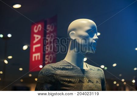 Discount store boutique mannequin with clothes on sale male figure portrait selective focus