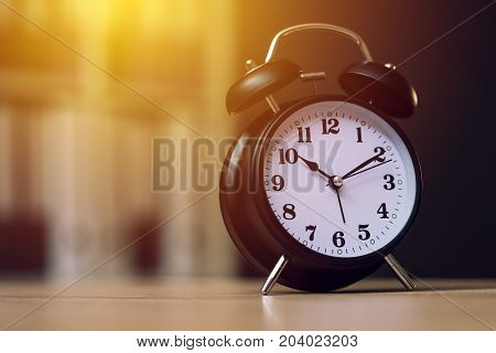 Classic alarm clock showing time during working hours or work break in business office selective focus