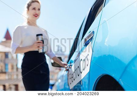 Eco friendly vehicle. Selective focus of an electric car being opened by a pleasant nice confident businesswoman