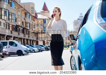 Business issues. Beautiful nice smart businesswoman standing on the street and having a phone conversation while opening her car