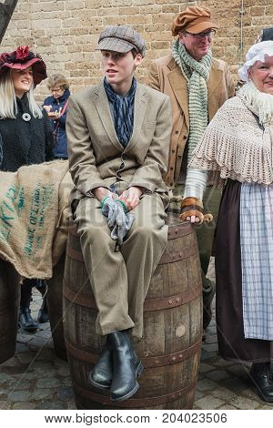 Deventer Netherlands - December 18 2016: Boy sitting on a barrel one of the characters from the famous books of Dickens during the Dickens Festival in Deventer in The Netherlands