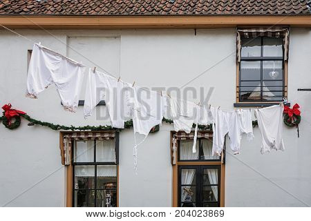 White laundry attached to a laundry line above the street