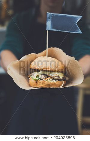 Street fast food festival, hamburger cooked at barbecue outdoors. Cookout american bbq food, closeup in chef's hand in craft paper, copy space
