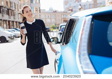 Positive mood. Joyful attractive smart businesswoman opening her car and smiling while having a thermo cup in her hands