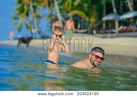 Happiness Portrait In Tropical Water: Seven Years Old Blond Boy Sitting In Water And His Brown-haire