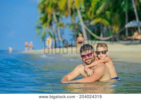 Close-up Portrait Of A Men And His Son In Water: Seven Years Old Cutest Blond Boy Hugged Gently His