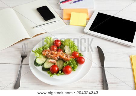 Healthy business lunch in the office, salad on white wooden desk near laptop computer keyboard. Salad bowl, juice, mobile phone and notepad with pen flat lay. Snack at break time