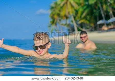 Close-up Portrait In Tropical Water: Seven Years Old Cutest Blond Boy Lying On The Water Surface, He