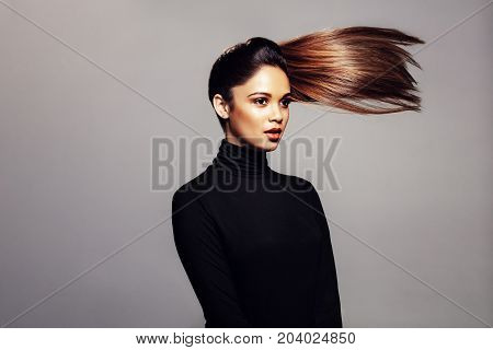 Studio shot of beautiful female against over grey background with hair ponytail flying in air. Woman fashion model with long hair looking away.