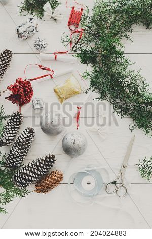 Creative diy craft hobby. Making handmade christmas wreath and fir tree garland. Tools and trinkets for holiday decorations. Top view of white wooden table with copy space.