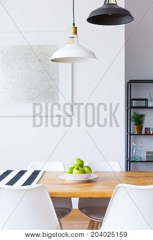 Lamps above dining table with apples and white chairs in contrast color room with painting