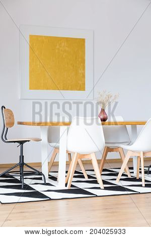 White chairs at dining table on patterned carpet in modern gold dining room with painting on white wall