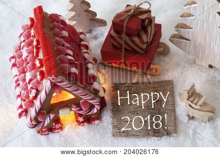 Label With English Text Happy 2018 For Happy New Year. Gingerbread House On Snow With Christmas Decoration Like Trees And Moose. Sleigh With Christmas Gifts Or Presents.