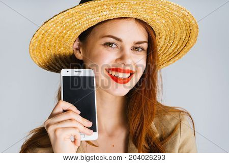 A young red-haired woman in a hat and with red lipstick shows a black screen of the phone in the camera, a mosk up and smiles