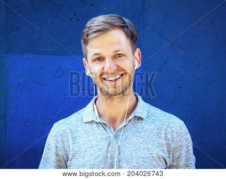 Portrait of happy handsome young guy standing against blue wall.