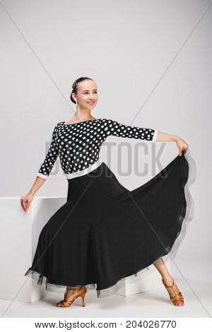 pretty woman in black dress in studio, dancer posing and looking up